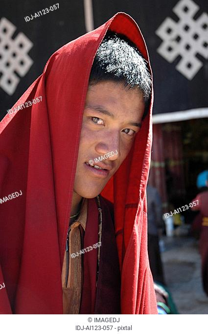 Close-up of a young man in a red shawl