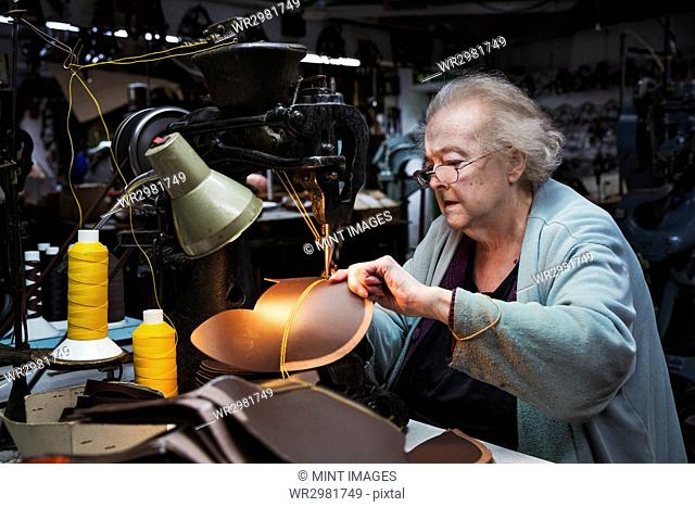 A grey haired senior worker of over 80 years old, a woman sitting at a sewing machine in a shoemaker's workshop