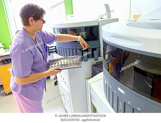 Laboratory worker adjusting microscope slides for purpose of analysis in staining platform in hospital, Anatomic Pathology, Hospital Donostia, San Sebastian