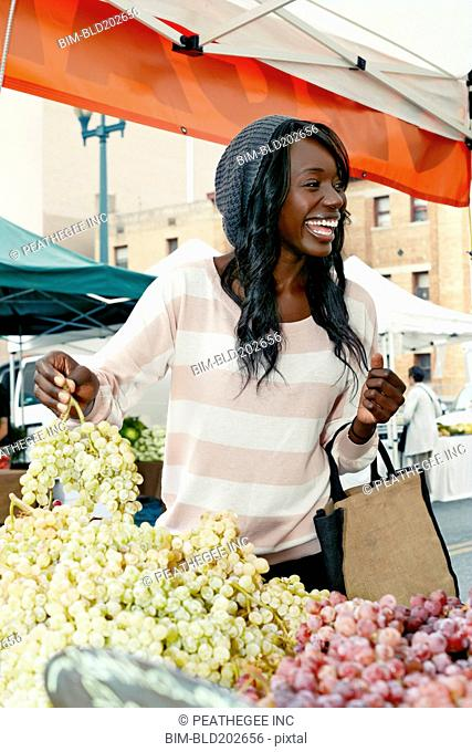African American woman buying grapes