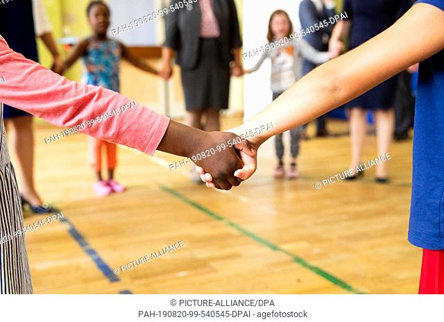 07 August 2019, Hamburg: Children and teachers dance hand in hand during a movement game in the gym of a day care centre