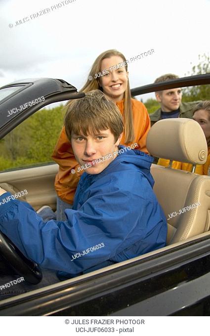 Teenage boy driving convertible