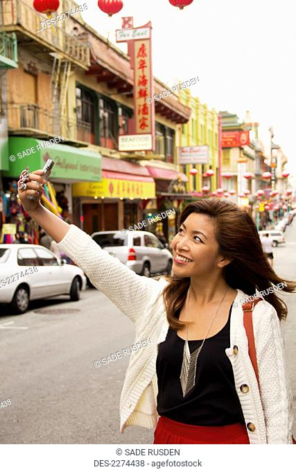 A woman takes a picture of herself with her cell phone camera in a busy urban area, san francisco california united states of america