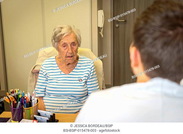 Reportage in an osteopathy practice in Héyrieux, France. Osteopathy session for a 98-year old woman suffering from back and arthritis pain