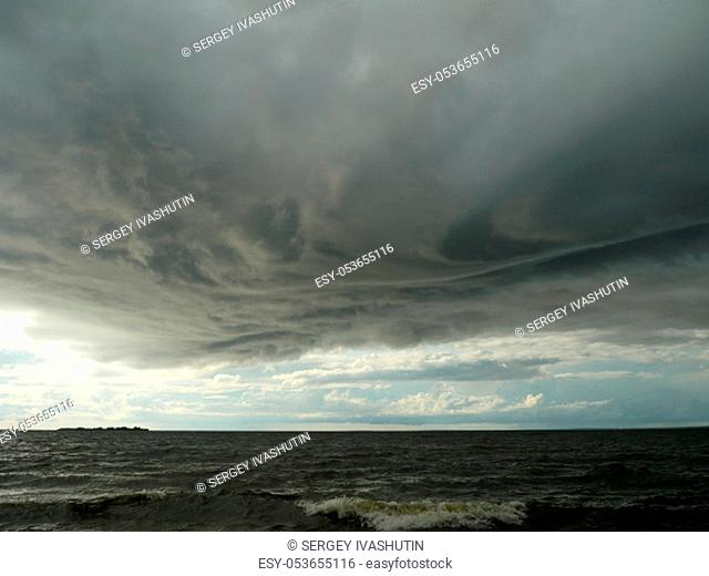 huge low dark clouds approaching the shore from the sea