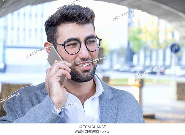 Portrait of smiling young businessman on the phone