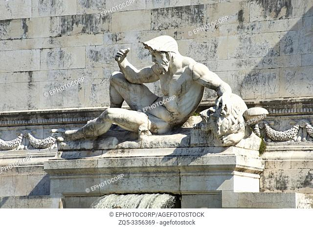 A statue of a strong reclining figure over an old building, Florence's Accademia museum, Florence, Italy