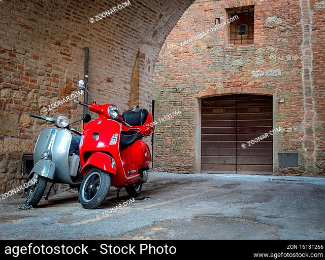 Montepulciano, Italy- October 3 2017: Red and grey vintage Vespa motorbikes parked on the streets of Montepulciano in Tuscana, Italy