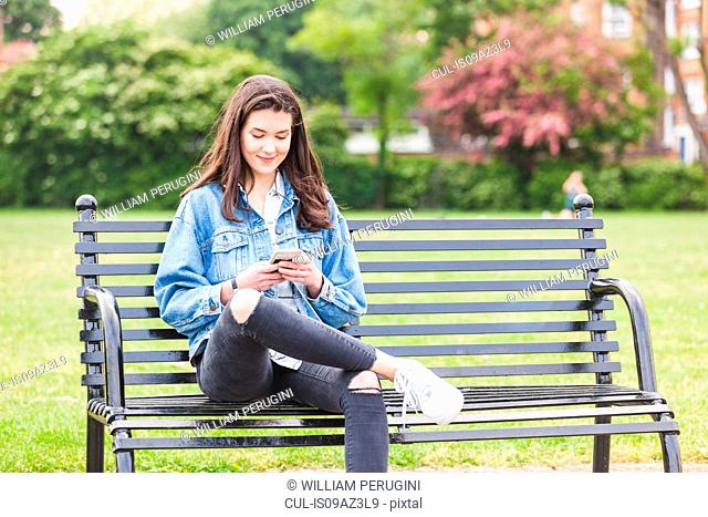 Young woman reading smartphone texts on park bench