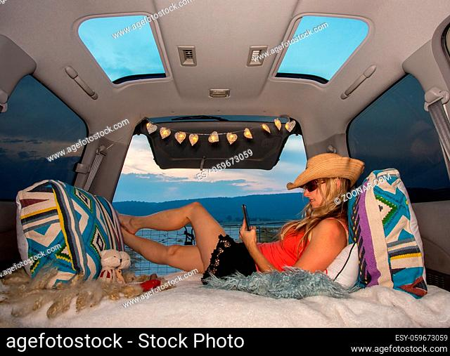 Woman relaxing in her van near mountains, using her mobile phone