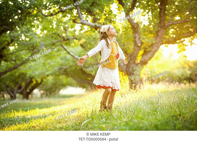 Carefree girl spinning in orchard with outstretched arms