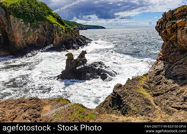 08 July 2020, Denmark, Allinge: The Camelhovederne and Lövehovederne (Camel head and Lion head rocks) rise from the Baltic Sea on the cliffs below the castle...
