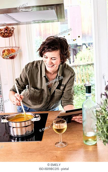 Mid adult woman stirring pot on stove in kitchen, holding digital tablet, laughing