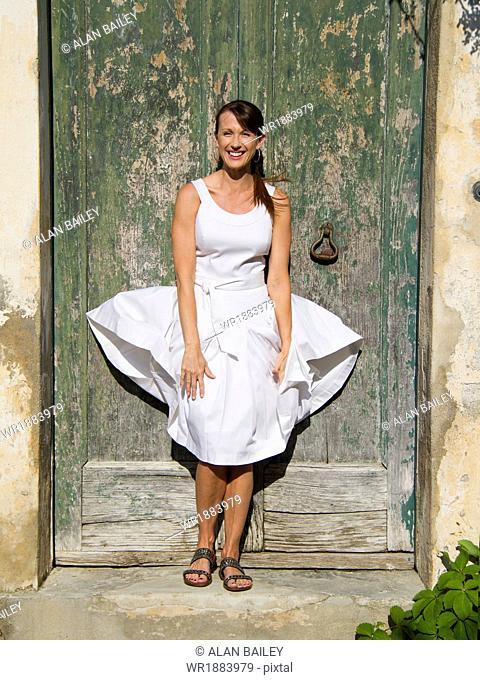 Italy, Ravello, Portrait of woman standing in front of watered wooden door, wind blowing woman's dress