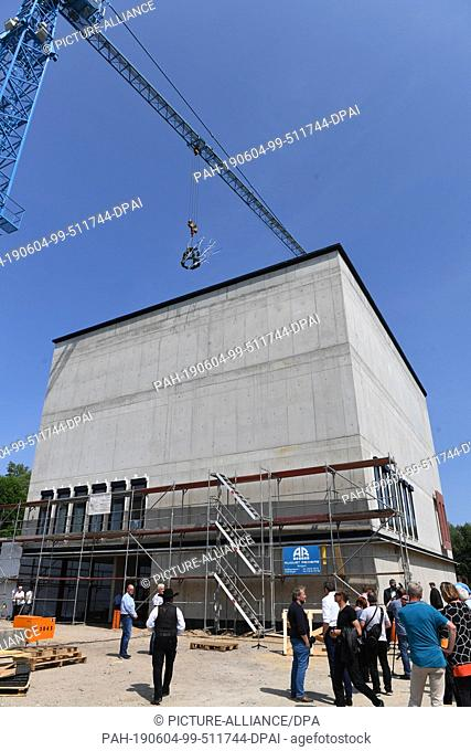 04 June 2019, Mecklenburg-Western Pomerania, Greifswald: A topping-out crown floats on a crane above the new building in Greifswald