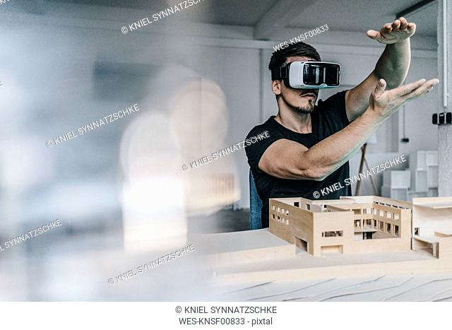 Man with architectural model and VR glasses