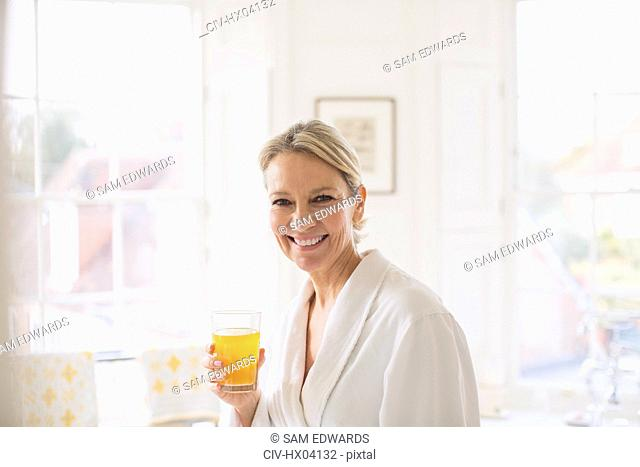 Portrait smiling, confident mature woman in bathrobe drinking juice