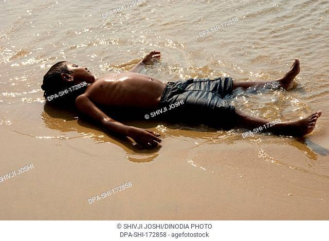 Boy lying down on anjuna beach , Goa , India