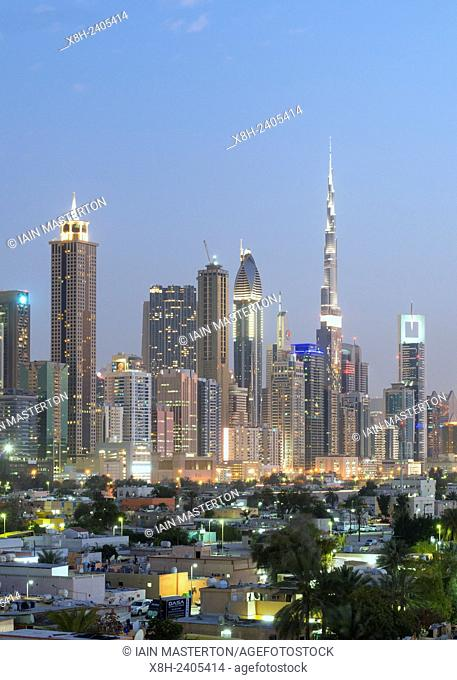 Night view across Satwa old town to skyline of skyscrapers along Sheikh Zayed Road in Dubai United Arab Emirates