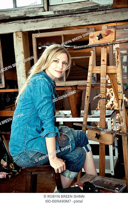 Mid adult woman sitting in artist's studio, portrait