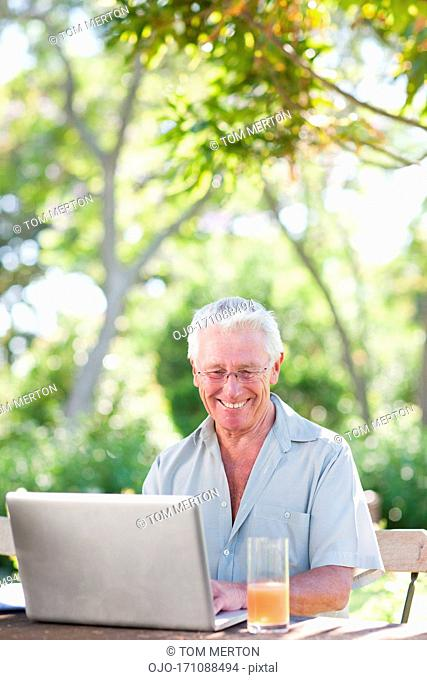 Senior man using laptop in garden