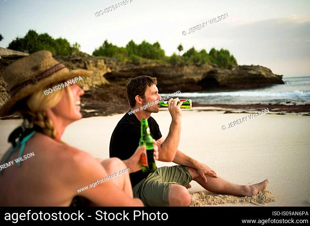 Couple sitting on beach, drinking beer, Nusa Lembongan, Indonesia