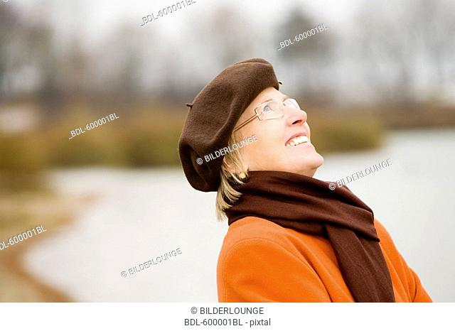 6c420111be80f portrait of mature woman wearing brown beret standing at lake in park
