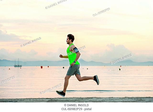 Side view of man jogging on beach, Mallorca, Spain