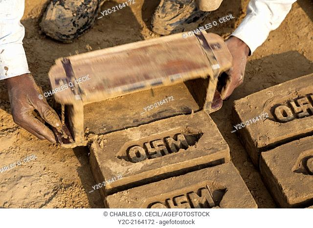 Rajasthan, India. Man Removing Mold from Newly-formed Brick. Note the Hindu Swastika on the Company Logo