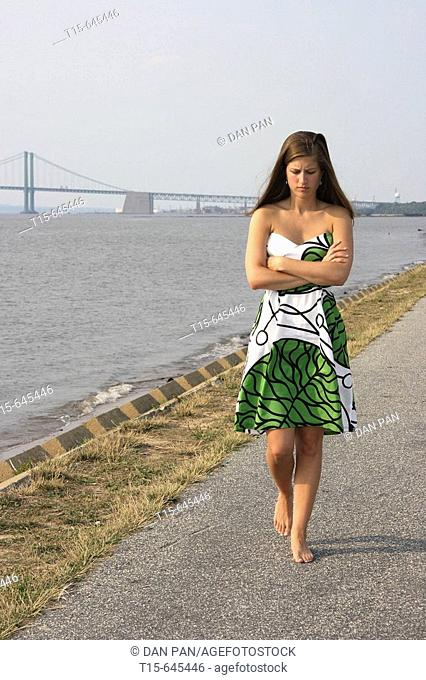woman in her 20's walking along a river bank pondering, contemplating and looking depressed and mad