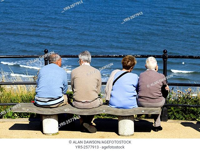 Elderly couples sitting on seat overlooking sea at Saltburn by the Sea, North Yorkshire, England, United Kingdom