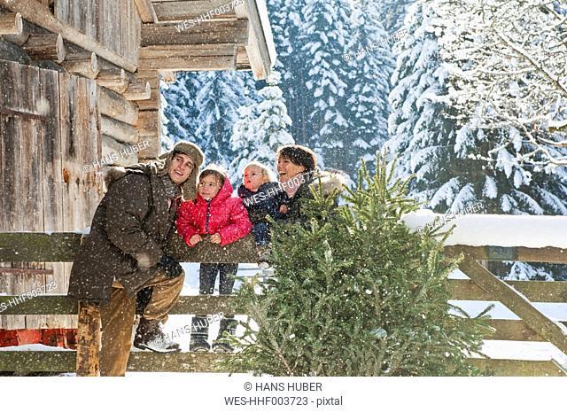 Austria, Salzburg Country, Flachau, Family leaning on fence in snow