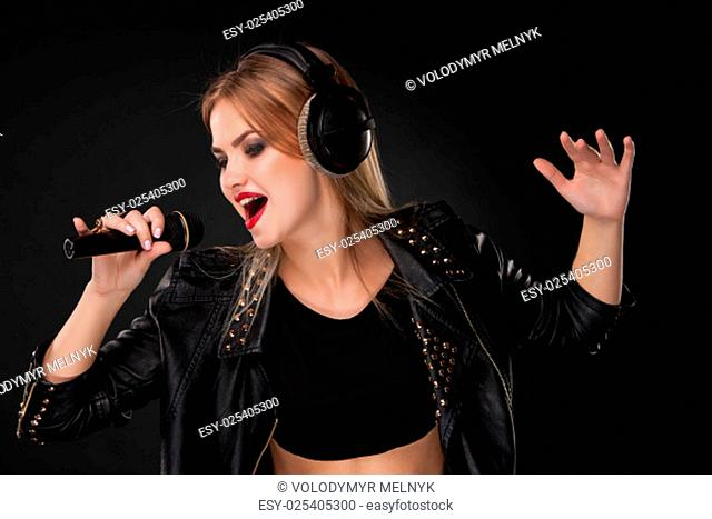 Portrait of a beautiful blonde young woman singing into microphone with headphones in studio on black background