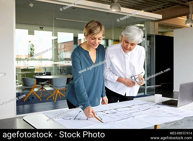 Two businesswomen working together on construction plan in office