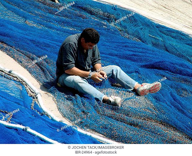ESP, Spain, Balearic Islands, Mallorca : Fisherman patches fishing nets in Port de Soller