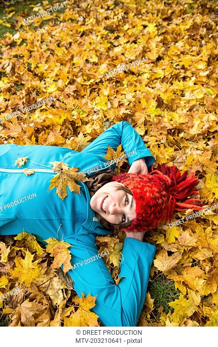 Smiling woman lying on ground in heap of autumn leaves