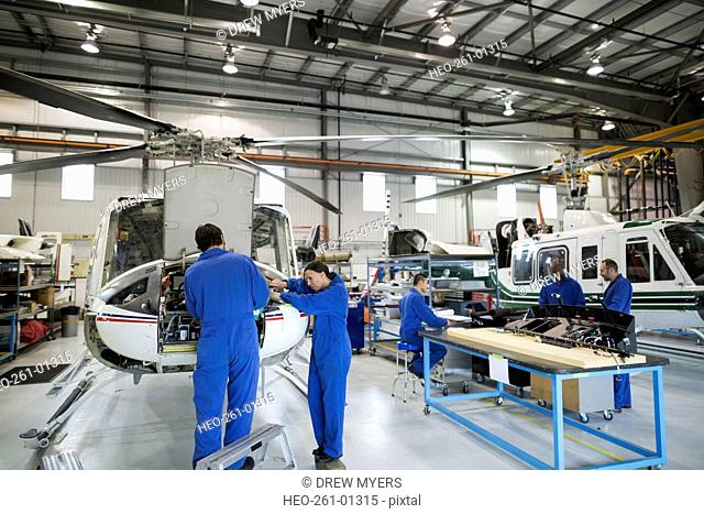 Mechanics repairing helicopter engine in airplane hangar