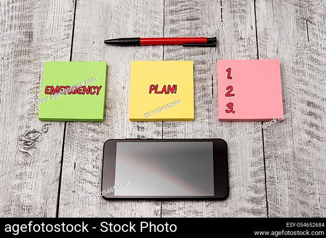 Writing note showing Emergency Plan. Business concept for actions developed to mitigate damage of potential events Stationary equipment and phone with paper...