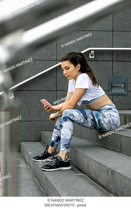Fit young woman sitting on stairs using cell phone