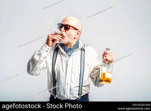 Fashionable elderly man with cigar and bottle of good alcohol, grey background. Mature senior looking at camera in studio, dude