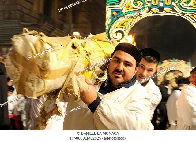 Italy, Sicily, Catania, man carrying candle during Sant'Agata Feast the Patron Saint of the city