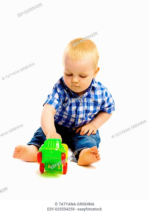 A little boy in a plaid shirt and jeans with toys on a white background