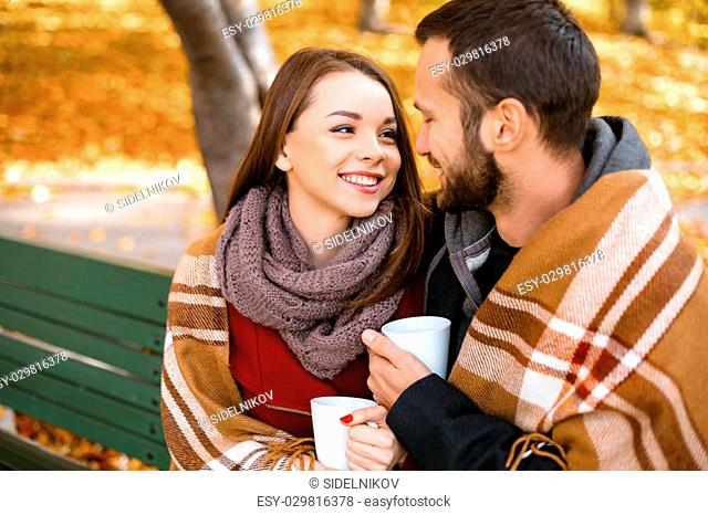 Romantic photo of cute couple outdoors in fall. Young man and woman sitting on bench with blanket and holding cups of coffee or tea