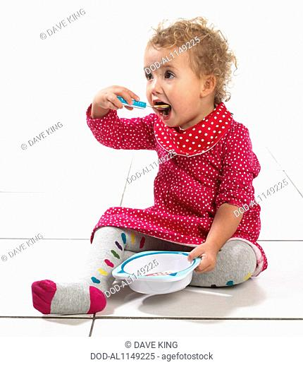 Girl (2 years) holding bowl and eating from spoon