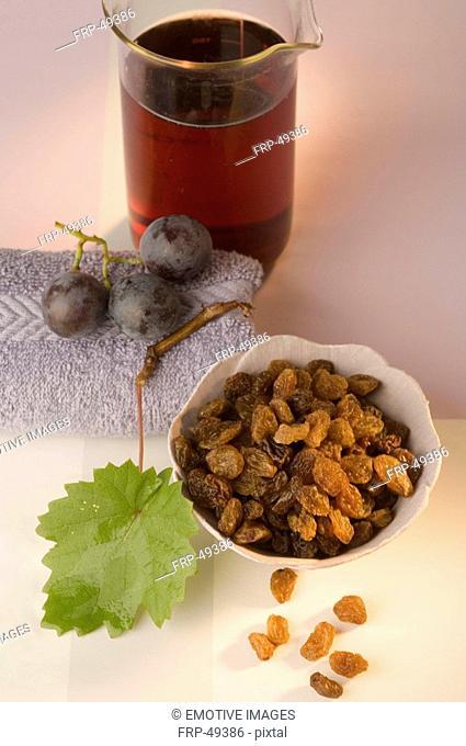 Glas mit Traubenkernöl aus roten Trauben und Rosinen in einer weißen Schüssel