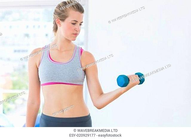 Young woman exercising with dumbbell in fitness studio