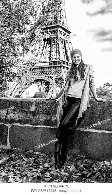 Autumn getaways in Paris. Full length portrait of happy young tourist woman on embankment near Eiffel tower in Paris, France