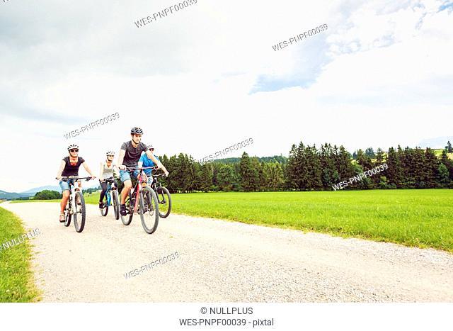 Germany, Bavaria, Pfronten, family riding mountain bikes in the countryside
