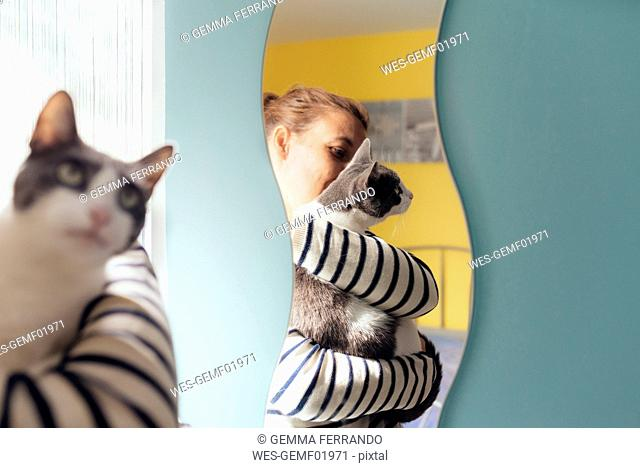 Woman holding a gray cat next to a mirror at home
