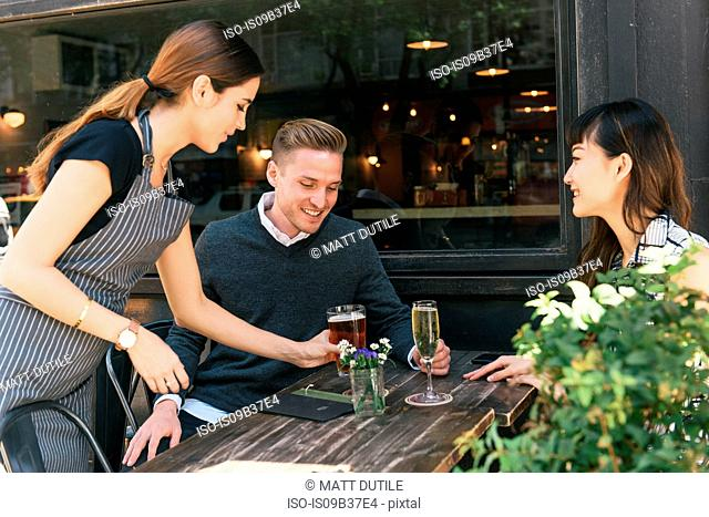 Waitress serving young couple outside restaurant
